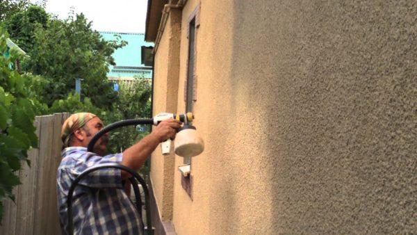 Процесс покраски фасада распылителем